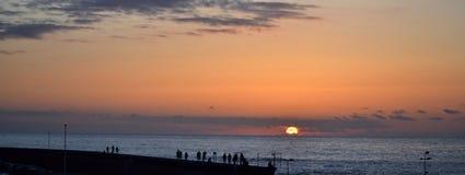 People watching the sunset on Atlantic Ocean shore. People silhouettes watching the sunset on Atlantic Ocean shore Royalty Free Stock Photos