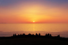 People watching the sunset on the sea Stock Image