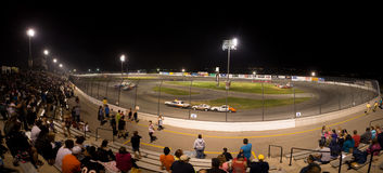People watchting a stock car competition at night Royalty Free Stock Photos