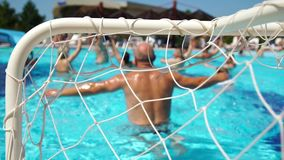 People water polo play in the pool, conceptual of a summer vacation and travel. People swimming in the cool blue water, conceptual of a summer vacation and stock video footage