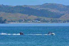 People water skiing over Mercury Bay New Zealand Stock Images