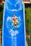 People water slide at aqua park. People having fun, water sliding at aqua park Royalty Free Stock Photography