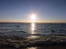 People in the water watch dramatic Sunset on San Souci Beach Royalty Free Stock Photos