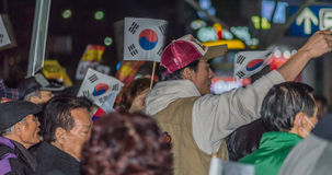 People wave flags in support of President Park Guen-Hye. SEOUL, South Korea, November 19,2016 Group of protesters outside Seoul Station rally against impeachment royalty free stock image