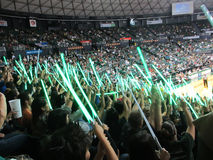 People wave light sabers in the air to distract free throw shoot. HONOLULU - FEBRUARY 12: People wave light sabers in the air to distract free throw shooter stock images
