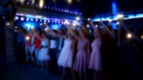 People wave their arms and hold light from flashlights in a nightclub, background, slow motion, stage for performance