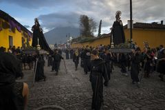 People wearing black robes and hoods in a street of the old city of Antigua during a procession of the Holy Week with a volcano in. Antigua, Guatemala - April 19 Royalty Free Stock Image