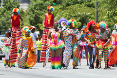 People Wearing Clown Costumes Walk In Caribbean Culture Parade. Atlanta, GA, USA - May 28, 2016:  People wearing colorful clown costumes and walking on stilts Stock Images