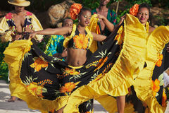 People wearing colorful dresses perform traditional creole Sega dance at sunset in Ville Valio, Mauritius.