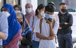 People wearing a face mask while lining up with social distancing