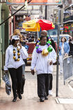 People wearing funny costumes celebrating famous Mardi Gras carnival on the street in French Quarter. Royalty Free Stock Photos