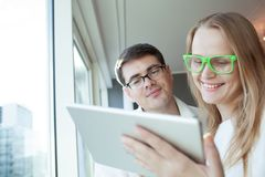 People Wearing Glasses with Tablet PC. Man and women in glasses are standing by window and watching something in tablet PC royalty free stock image