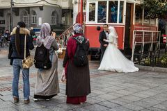 People wearing islamic scarf taking wedding pictures with smartphones of a newly married couple stock photo