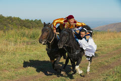 People wearing national dresses ride on horseback at countryside, Almaty, Kazakhstan. Stock Photos