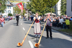 People wearing traditional clothes and playing the alphorn at En Stock Photography