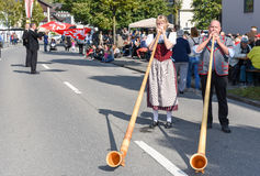People wearing traditional clothes and playing the alphorn at En Royalty Free Stock Images