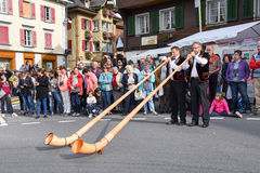 People wearing traditional clothes and playing the alphorn at Ke Stock Image