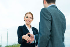 People welcoming with business handshake. Business handshake - two businesspeople shaking hands to conclude deal or agreement Stock Photo