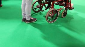 People, wheelchair on green. People walking, caretaker pushing wheelchair on green background stock footage