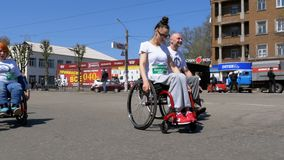 People in wheelchairs athletes participating in the marathon. Slow Motion. Kamenskoye, Ukraine, April 21, 2018: People in wheelchairs athletes participating in stock footage
