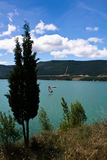 People windsurfing on artificial turquoise lake Royalty Free Stock Images