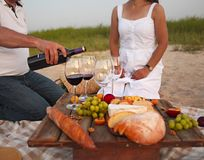 People at wine outdoor party. Man pouring red wine in to the win Stock Photo