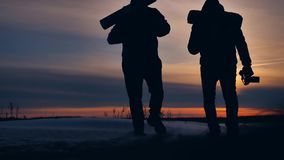 People winter background blur silhouette snow sunlight. group of tourists walking on top of a sunset silhouette mountain. People winter background blur stock footage