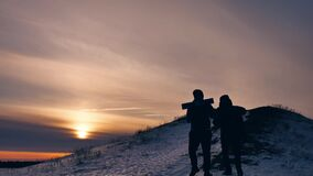 People winter silhouette snow sunlight. group of tourists walking on top of a sunset silhouette mountain. slow video. People winter silhouette snow sunlight stock footage