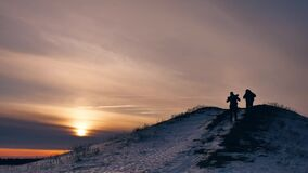 People winter silhouette snow sunlight. group of tourists walking on top of a sunset silhouette mountain. slow video. People winter silhouette snow sunlight stock video footage