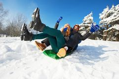 People in winter. young smiling couple sledding Royalty Free Stock Photography