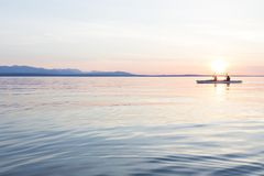 People women sea kayaking paddling boat in calm water together at sunset. Active outdoor adventure water sports. Journey,. Destination, teamwork concepts stock photos