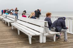 People at wooden pier Cuxhaven waiting for ferry to Helgoland. Royalty Free Stock Images