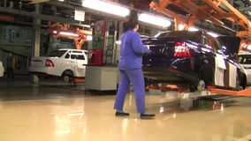 People work at assembly of cars Lada on conveyor of factory AutoVAZ stock video footage