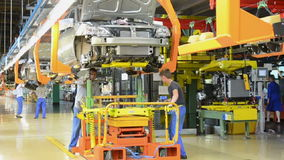 People work at assembly of cars Lada Kalina on conveyor of factory AutoVAZ
