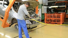People work at assembly of cars LADA Largus on conveyor of factory stock video footage
