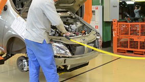People work at assembly of cars LADA Largus on conveyor stock footage