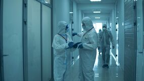 People work at clinic, wearing protective suits during pandemic.