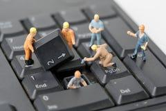 People Work on Computer Keyboard. Miniature people Work on Computer Keyboard Stock Images