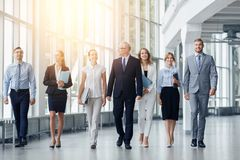 Business people walking along office building stock images