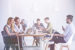 People during work. Happy young people sitting at the desk during work Stock Images