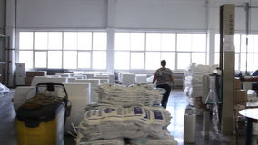 People work in large warehouse with goods at factory. VOLZHSKY, Russian Federation - OCTOBER 27, 2014: People work in large warehouse with goods at factory stock footage