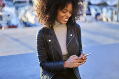 People at work navigator via smartphone and fast 4G internet in roaming. Young beautiful afro american  female tourist with curly hair strolling on city streets Royalty Free Stock Image