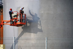 The people at work and paint spraying large container for oil and petrol Stock Images
