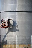 The people at work and paint spraying large container for oil and petrol Royalty Free Stock Image