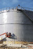 The people at work and paint spraying large container for oil and petrol Stock Photography