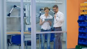 Two workers use a tablet. People work in a room, using one tablet stock footage