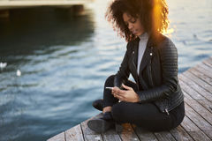 People at work using smartphone and 4G internet in roaming. Attractive pensive afro-American female tourist leather jacket  blogging site writing article about Royalty Free Stock Photography