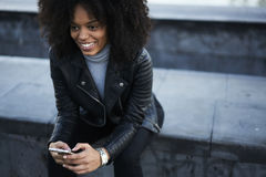 People at work and wireless connection to internet in free wifi zone outside. Smiling Afro-American hipster girl in good mood booking room in hotel preparing for Royalty Free Stock Image