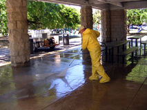 People Workers Man cleaning Sidewalk using Power Sprayer. In a Environmental Hazard Suit Royalty Free Stock Images
