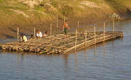 People working around a river unique editorial photo. A group of people working with a bamboo made structure in the river water unique photo stock image